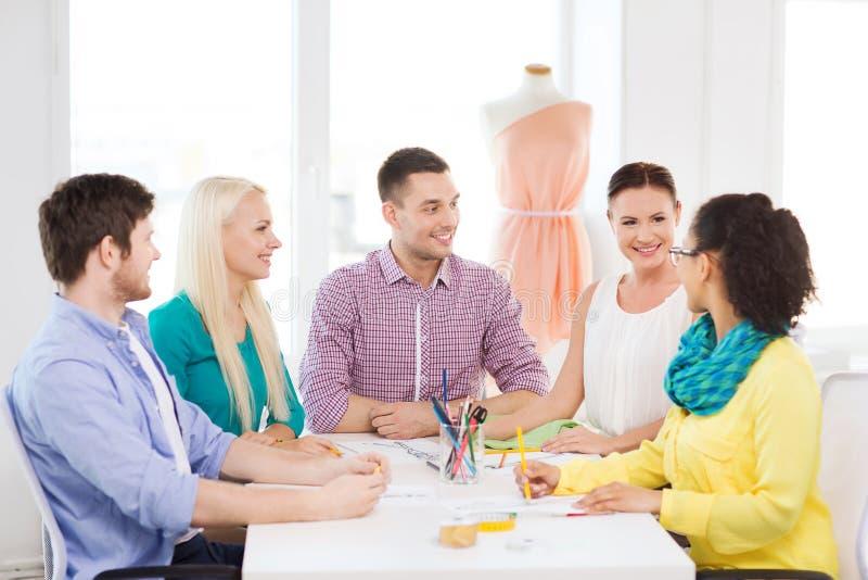 Lächelnde Modedesigner, die im Büro arbeiten lizenzfreies stockfoto