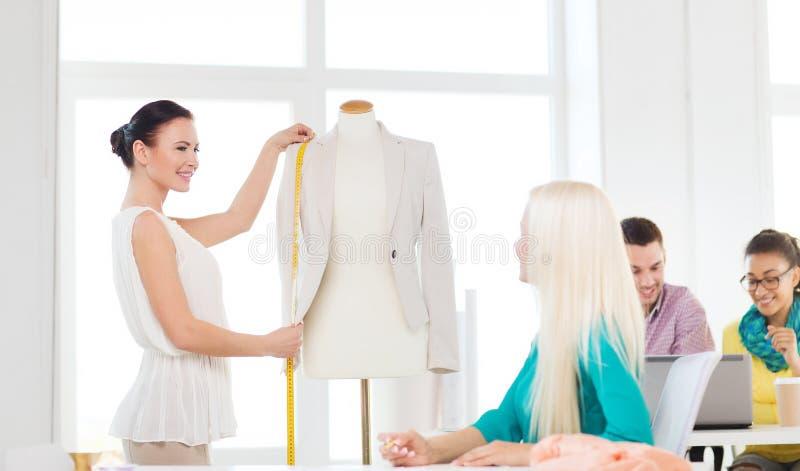 Lächelnde Modedesigner, die im Büro arbeiten lizenzfreie stockfotografie