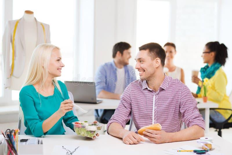 Lächelnde Modedesigner, die im Büro zu Mittag essen stockfoto