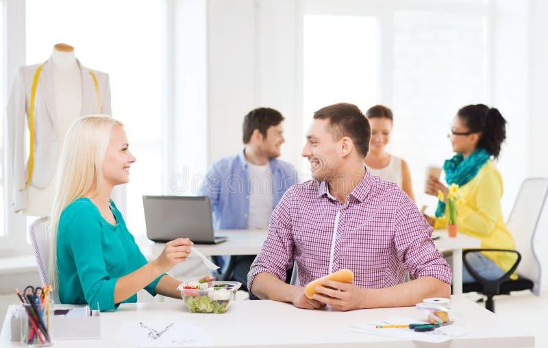 Lächelnde Modedesigner, die im Büro zu Mittag essen lizenzfreie stockbilder