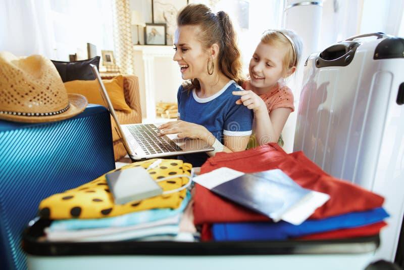 Lächelnde moderne Mutter- und Kinderreisende, die Flugscheine kaufen stockfoto