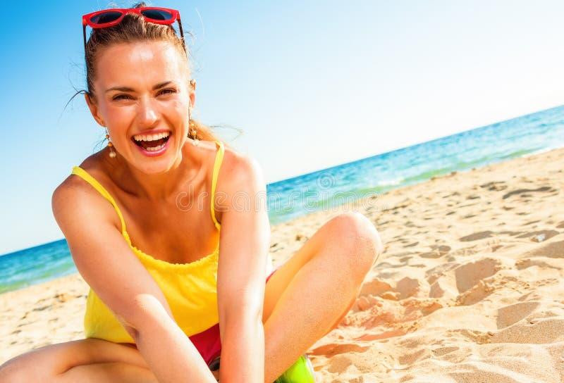 Lächelnde modische Frau im bunten Kleid, das auf Strand sitzt lizenzfreie stockfotos