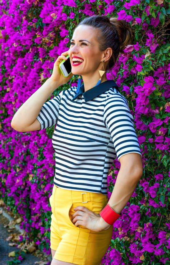 Lächelnde modische Frau nahe dem Blumenbett, das am Handy spricht lizenzfreies stockfoto