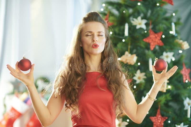 Lächelnde modische Frau nahe dem Weihnachtsbaum, der Yoga tut stockfoto