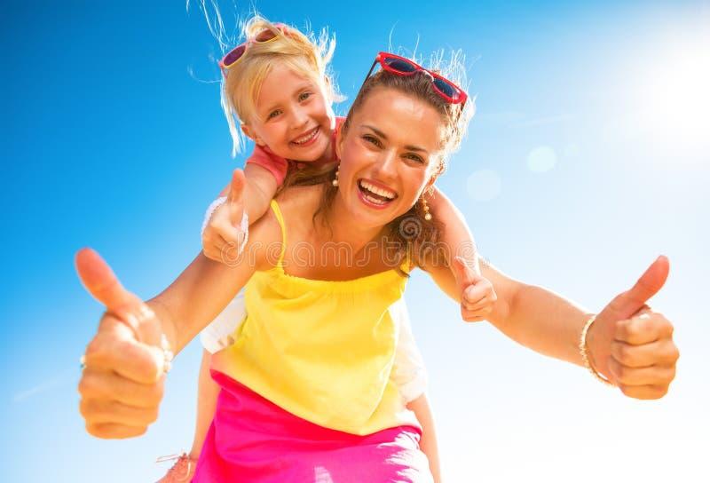Lächelnde modische Mutter und Kind auf dem Strand, der sich Daumen zeigt stockfotos