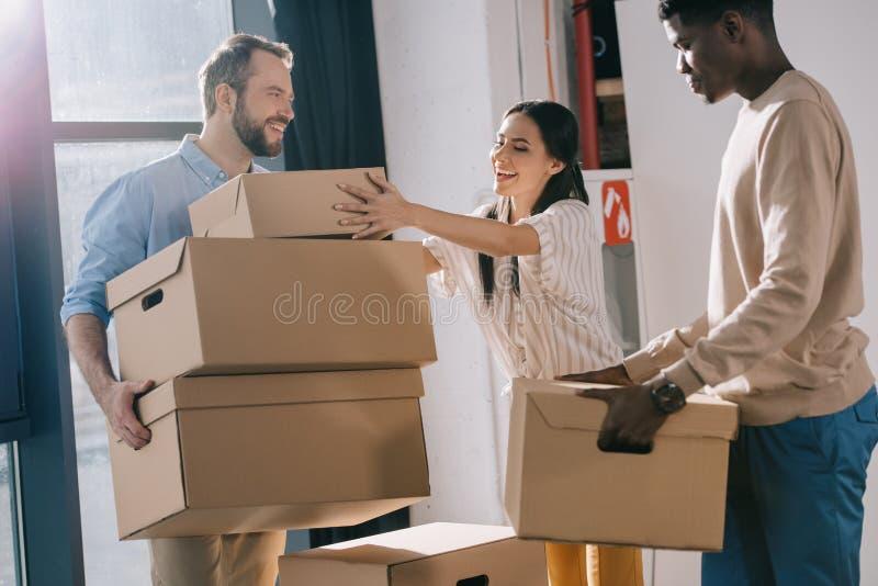 lächelnde multiethnische Mitarbeiter, die Pappschachteln während der Verlegung im neuen Büro tragen lizenzfreies stockbild