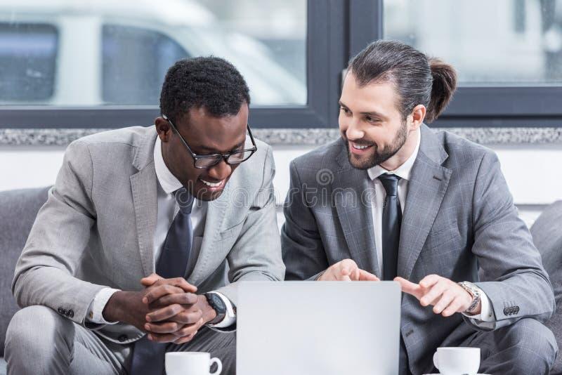 lächelnde multikulturelle Geschäftsmänner in den Klagen, die bei Tisch mit Laptop sitzen lizenzfreies stockbild