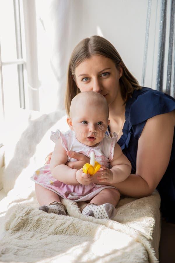 Lächelnde Mutter, die ihre Baby-Tochter am Fenster umarmt stockfotos