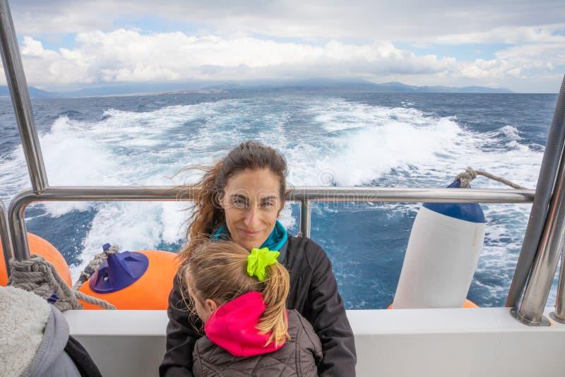 Lächelnde Mutter, die ihre Tochter im Motorboot im Ozean umfasst stockfoto