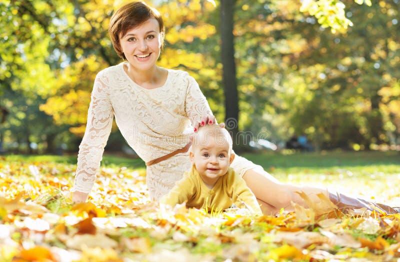 Lächelnde Mutter, die um Baby sich kümmert lizenzfreie stockbilder