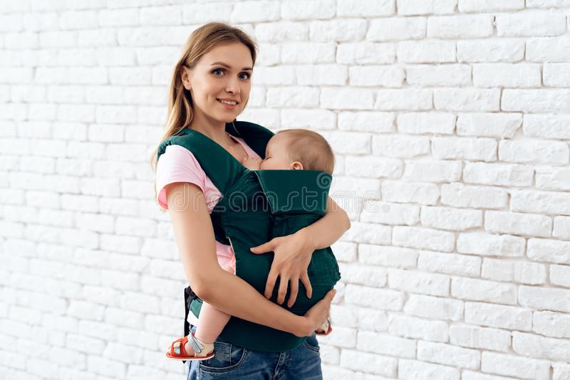 Lächelnde Mutter mit neugeborenem Baby im Babyriemen lizenzfreie stockfotos