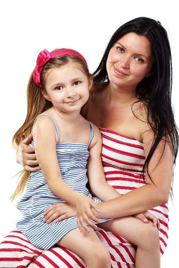 Lächelnde Mutter mit Tochter auf ihren Knien stockfotografie