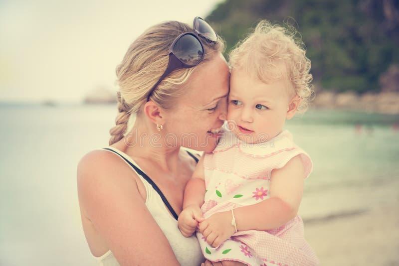 Lächelnde Mutter umarmt ihre kleine gelockte Tochter während im Urlaub am Strand lizenzfreies stockfoto