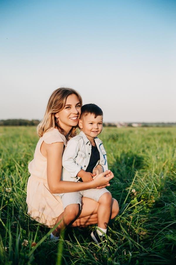 Lächelnde Mutter und Baby, die auf Wiese sitzen lizenzfreie stockfotos