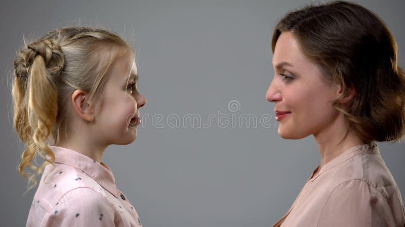 Lächelnde Mutter und Tochter, die einander, Reflexion heranwachsend betrachtet stockbild