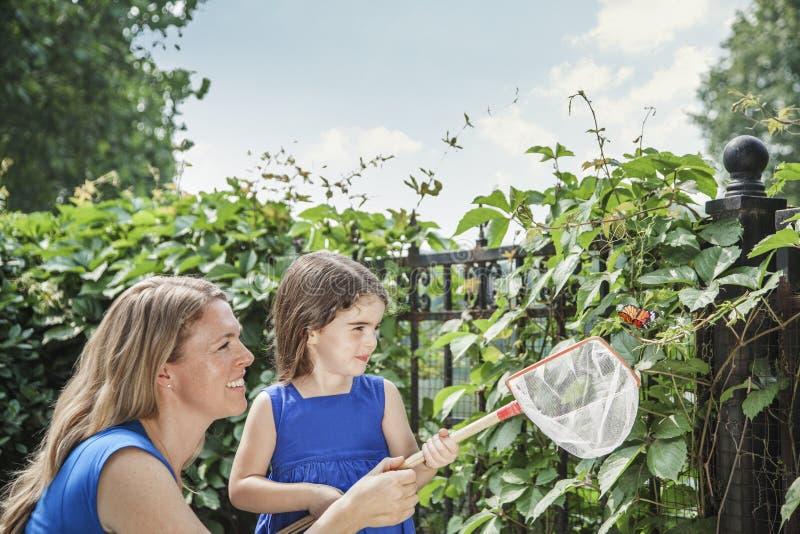 Lächelnde Mutter und Tochter, die einen Schmetterling halten und versuchen, einen Schmetterling im Garten zu fangen lizenzfreies stockbild