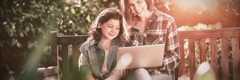 Lächelnde Mutter und Tochter, die Laptop beim Sitzen auf Holzbank verwendet lizenzfreie stockfotos