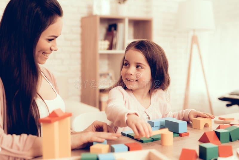 Lächelnde Mutter und Tochter, die Würfel auf Tabelle spielen stockfotos
