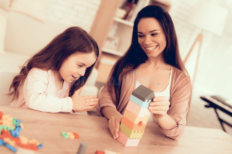 Lächelnde Mutter und Tochter, die Würfel auf Tabelle spielen lizenzfreie stockfotografie