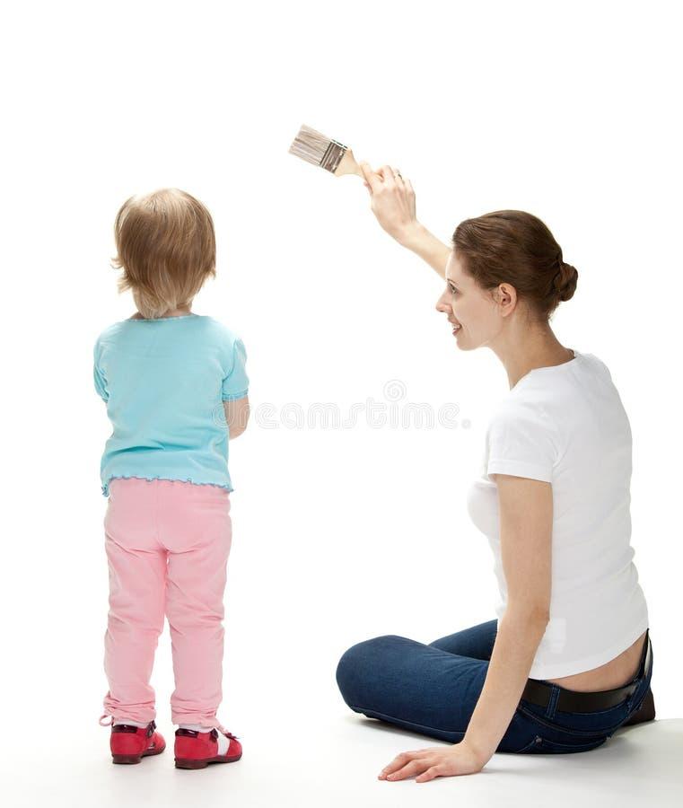 Lächelnde Mutter und Tochter, welche die Wand malen stockfotografie