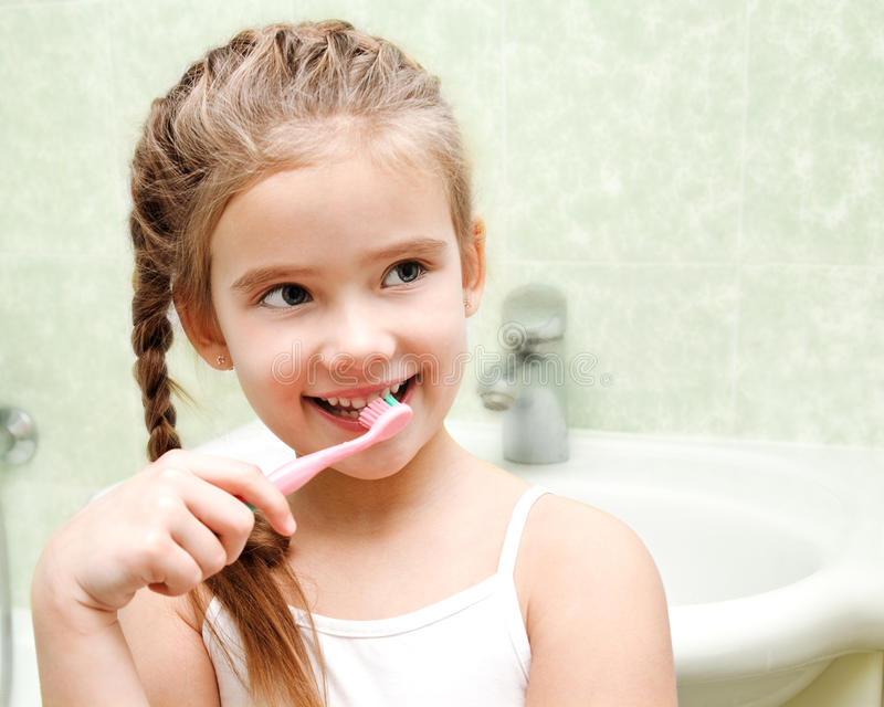 Lächelnde nette bürstende Zähne des kleinen Mädchens stockfotografie