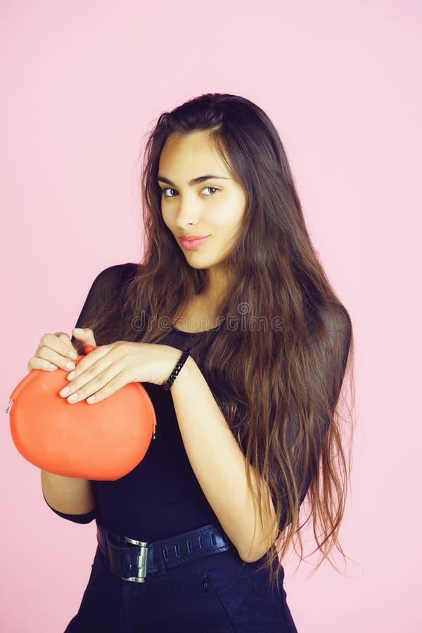 Lächelnde nette Frau, die mit rotem Geldbeutel, Tasche oder Handtasche aufwirft stockfotos