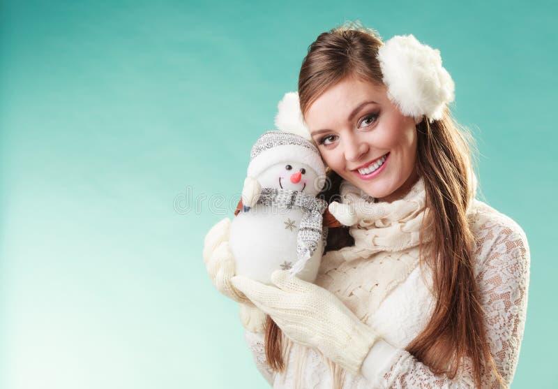Lächelnde nette Frau mit kleinem Schneemann Winter stockfoto