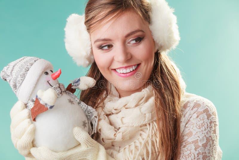 Lächelnde nette Frau mit kleinem Schneemann Winter stockbild