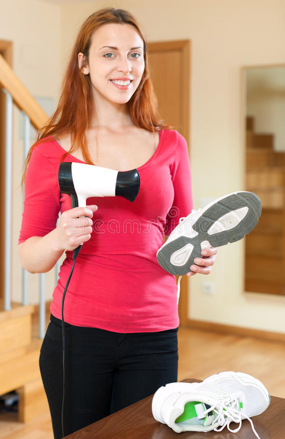 Lächelnde nette Hausfrau in rotem Heizungsturnschuhe hairdryer stockbild