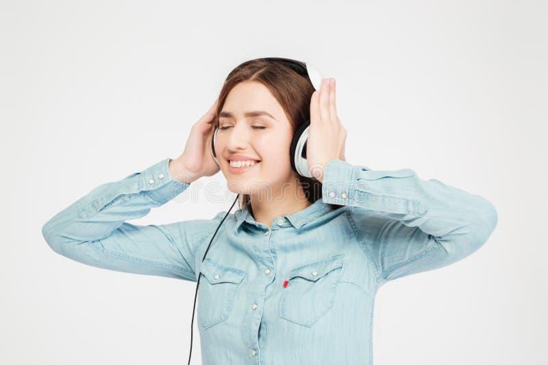 Lächelnde nette reizende Frau, die Kopfhörer verwendet und Musik hört stockbilder