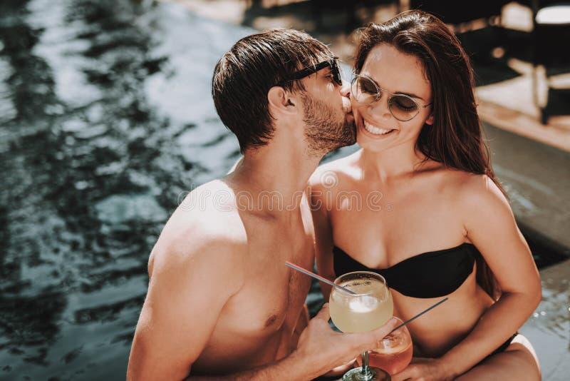 Lächelnde Paar-trinkende Cocktails am Poolside stockfotos