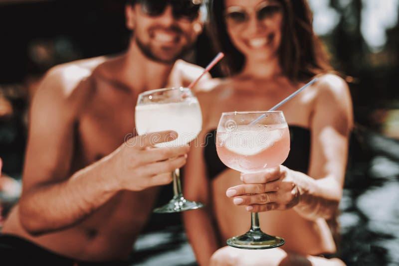 Lächelnde Paar-trinkende Cocktails am Poolside lizenzfreie stockfotografie