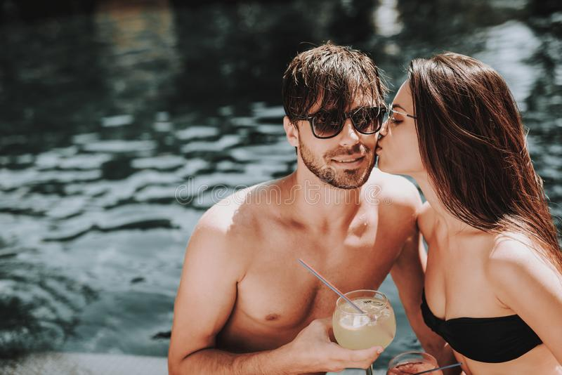 Lächelnde Paar-trinkende Cocktails am Poolside lizenzfreie stockbilder