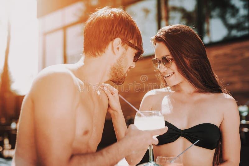 Lächelnde Paar-trinkende Cocktails am Poolside stockfotografie