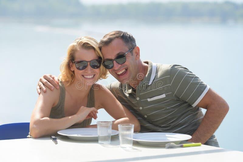 Lächelnde Paare beim Warten auf ihre Bestellung lizenzfreie stockfotos