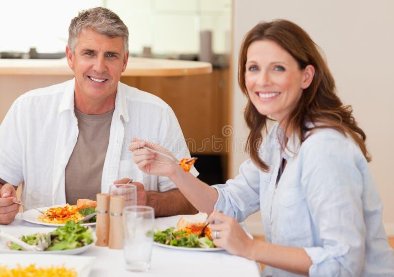 Lächelnde Paare, die Abendessen essen stockfotos