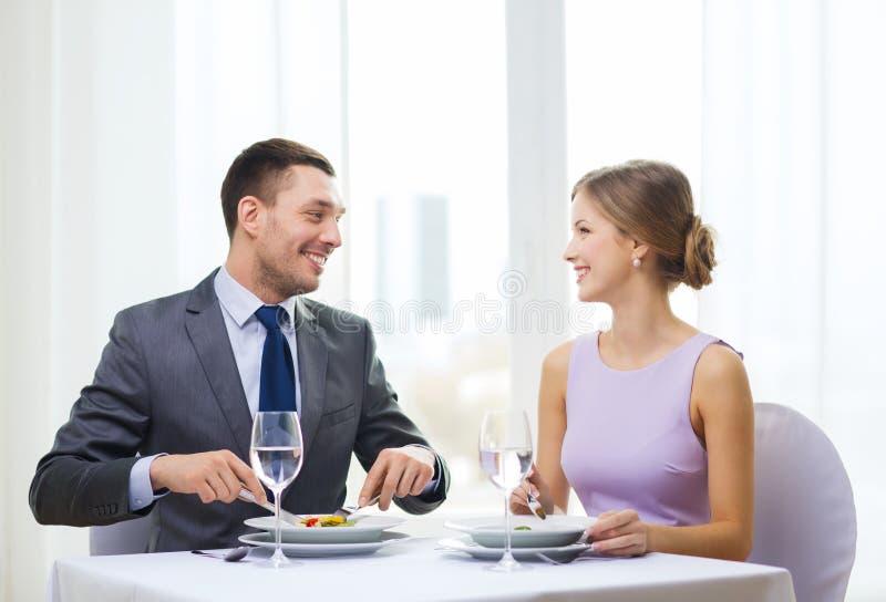 Lächelnde Paare, die Aperitifs am Restaurant essen lizenzfreies stockfoto