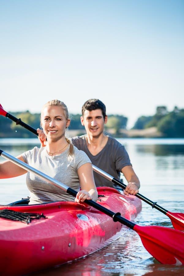 Lächelnde Paare, die auf See Kayak fahren stockfoto