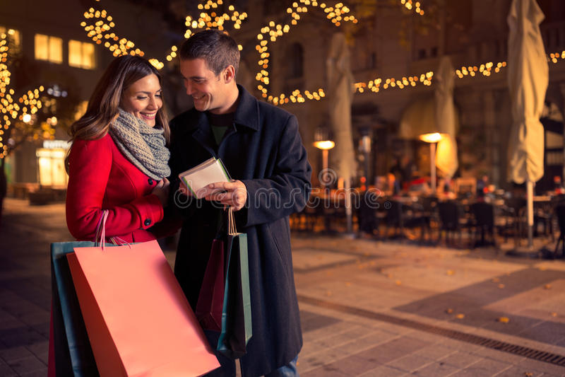 Lächelnde Paare, die Einkaufsliste auf Weihnachten überprüfen lizenzfreies stockbild