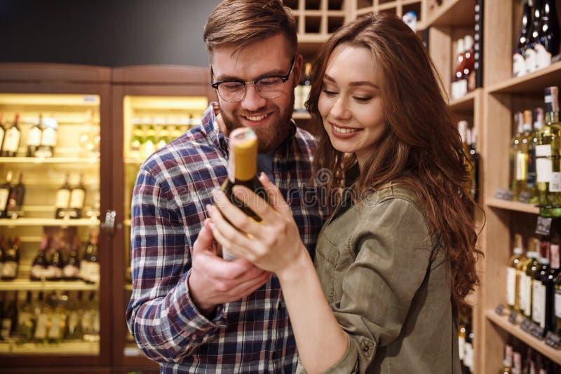 Lächelnde Paare, die Flasche Wein wählen stockbilder