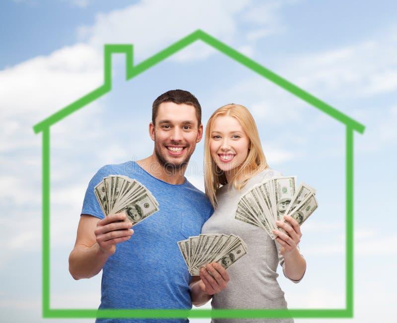 Lächelnde Paare, die Geld über grünem Haus halten stockfotos