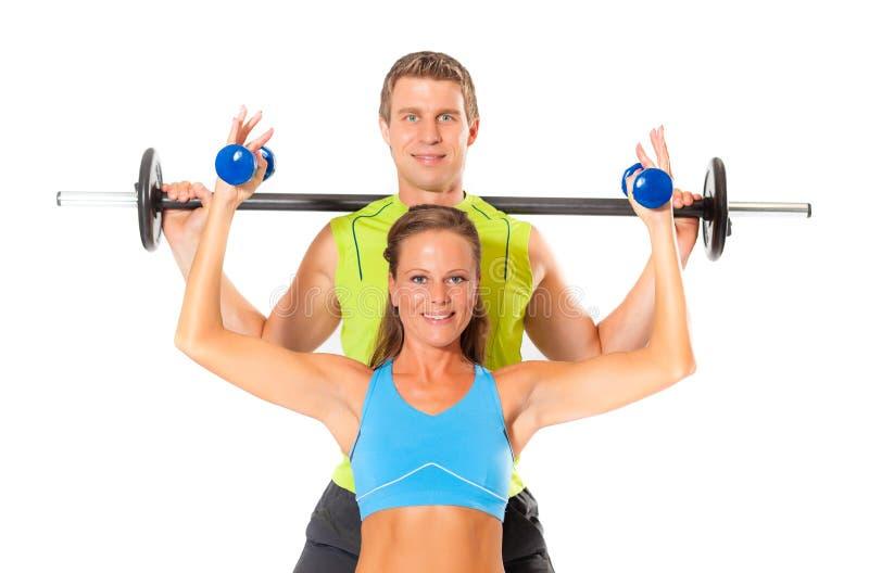 Lächelnde Paare, die Gewichthebenübung tun stockbild