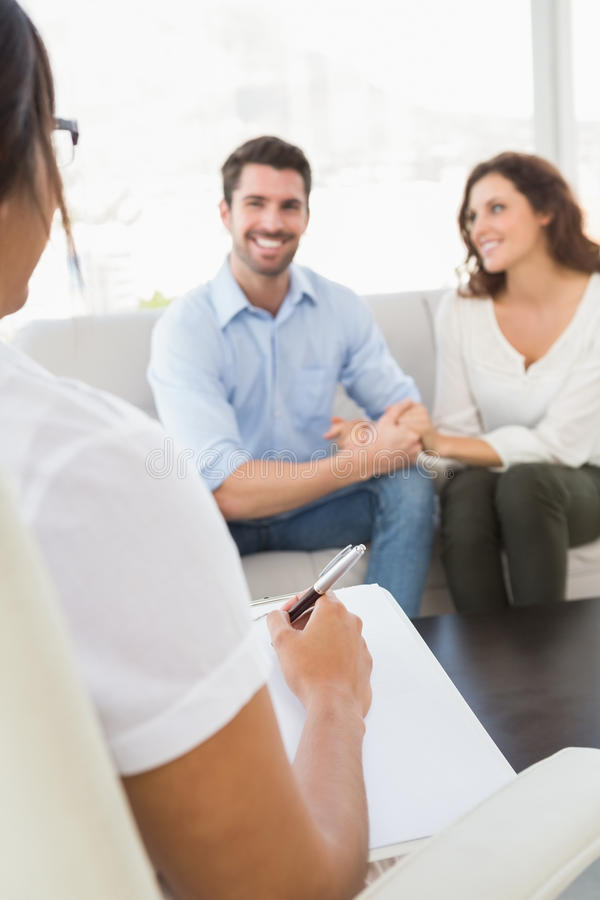 Lächelnde Paare, die mit ihrem Therapeuten sprechen stockfoto