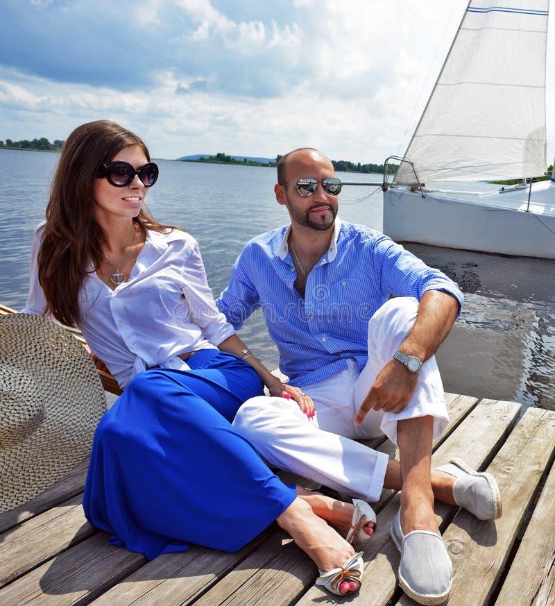 Lächelnde Paare, die nahe Wasser im Hafen sitzen stockbild