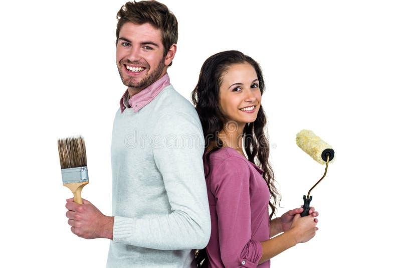 Lächelnde Paare, die Pinsel halten stockfotografie