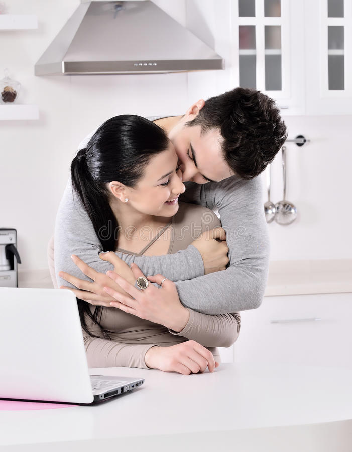 Lächelnde Paare, die rote Rebe im kitchev genießen lizenzfreie stockfotografie
