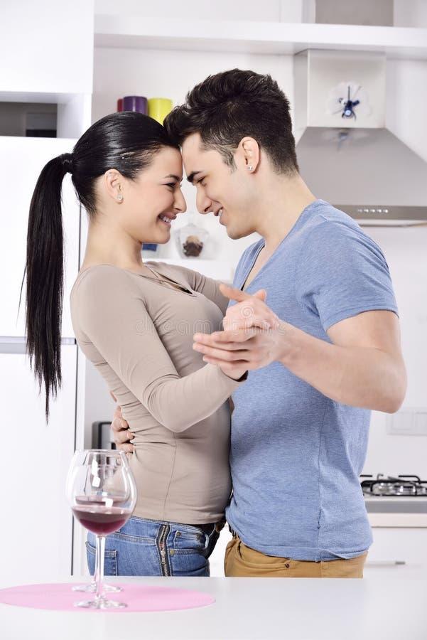 Lächelnde Paare, die rote Rebe im kitchev genießen lizenzfreies stockbild