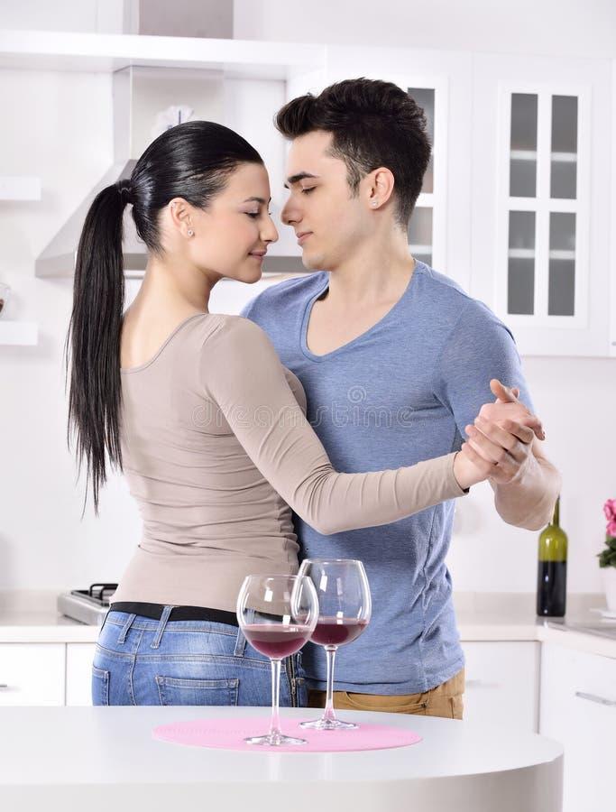 Lächelnde Paare, die rote Rebe im kitchev genießen stockfoto