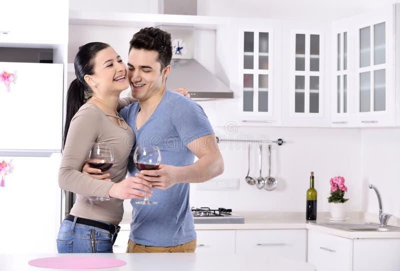 Lächelnde Paare, die rote Rebe im kitchev genießen stockbild