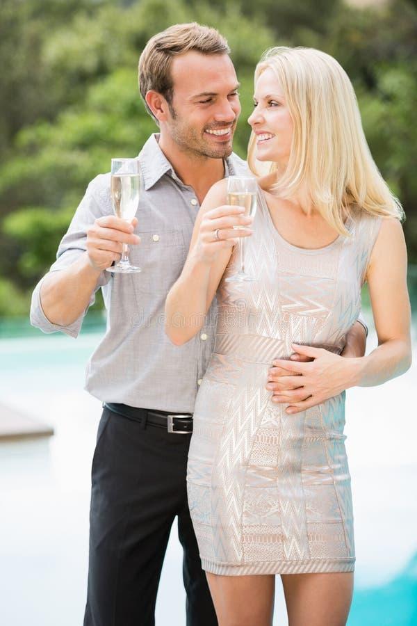 Lächelnde Paare, die Sektkelche am Poolside halten stockbild